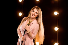 Young smiley beautiful long hair girl with microphone singing. Song on the stage in karaoke Royalty Free Stock Images