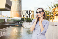 Young smiley Caucasian business woman is talking on the smart-phone near skyscrapers. Nice female with long brown hair is standing on the street and having Stock Photos