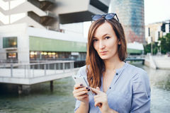 Young smiley well-dressed Caucasian business woman uses smart-phone. Stock Photo
