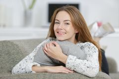 Young smiley woman hugging cushion. Young smiley woman hugging a cushion royalty free stock images