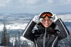 Young smiley woman skier. Young smiley woman in ski sunglasses over mountains landscape Royalty Free Stock Image