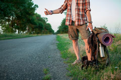 Young smilimg caucasian tourist hitchhiking along. Young smilimg caucasian tourist with backpack hitchhiking along a road in sunset Royalty Free Stock Images