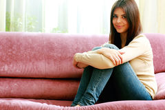 Young smilin woman sitting on the sofa Stock Photography