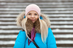 Young smiling adorable blond woman wearing blue hooded coat strolling in snowy winter city park. Nature cold season freshness conc Royalty Free Stock Images