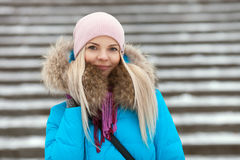 Young smiling adorable blond woman wearing blue hooded coat strolling in snowy winter city park. Nature cold season freshness conc. Ept Stock Image
