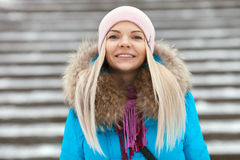 Young smiling adorable blond woman wearing blue hooded coat strolling in snowy winter city park. Nature cold season freshness conc. Ept Stock Photos