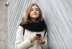 Young smiling adorable woman texting on smartphone posing against grey wooden garage doors. Lifestyle positive emotions concept. Stock Images