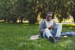 Young man listening to music on grass outdoors. Young smiling african-american man sitting on grass, using smartphone and listening to music with earphones Royalty Free Stock Image
