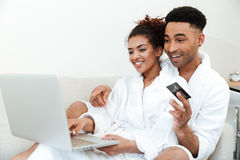 Young smiling african loving couple using laptop holding credit card. Royalty Free Stock Photography
