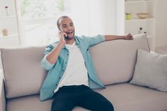 Young smiling african male student is talking on his phone, sitt. Ing relaxed on the cozy beige sofa at home in light modern room, wearing casual jeans outfit Stock Photo