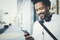 Young Smiling African man using smartphone on hands while standing at sunny city street.Concept of happy business people. Working outside.Blurred background Stock Photography