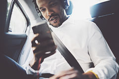 Young smiling african man using smartphone while sitting on backseat in car.Concept of happy business people traveling. Blurred background Stock Photos