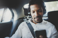 Young smiling african man using smartphone while sitting on backseat in taxi car.Concept of business people traveling Royalty Free Stock Photo