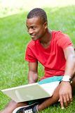 Young smiling african student sitting in grass with notebook Royalty Free Stock Photography