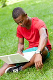 Young smiling african student sitting in grass with notebook Royalty Free Stock Photos