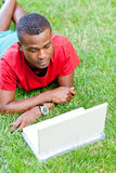 Young smiling african student sitting in grass with notebook Royalty Free Stock Images