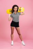 Young smiling african teenage girl standing and holding skateboard Stock Photo