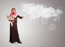 Young smiling arab with laptop shows virtual  icons of the cloud Stock Images