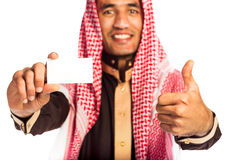 Young smiling arab showing business card in hand isolated on whi Stock Photo
