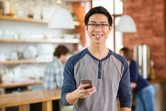 Young smiling asian boy in glases using smarphone Royalty Free Stock Photo