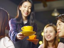 Young smiling asian waitress serving coffee to customers. Focus on the cup Stock Photography