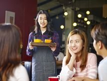Young smiling asian waitress serving coffee to customers. Young smiling asian waitress serving customers in coffee shop, focus on the background girl Stock Photography
