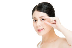 Young smiling asian woman eyes with finger clip gesture. Close up of young smiling asian woman eyes with finger clip gesture, isolated on white background Stock Image