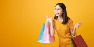 Young smiling asian woman holding multi coloured shopping bags and looking on light yellow background.