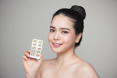 Young smiling asian woman with Omega 3 fish oil capsule Stock Photo