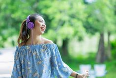 Young smiling asian woman listening to music with headphones Stock Images