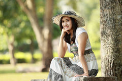 Young smiling asian woman sitting outdoor Stock Images
