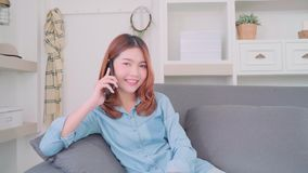Young smiling Asian woman talking on smart phone with friends while lying on the sofa when relax in living room at home. stock footage