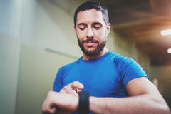 Young smiling athlete tracking burned calories on electronic smart watch application after good indoor workout session Royalty Free Stock Photography