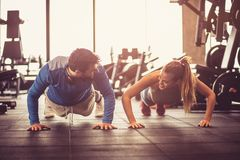 Push-ups i gym. Young smiling athletes exercising push-ups in a gym royalty free stock photography