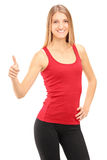 Young smiling athletic female giving a thumb up Stock Photography