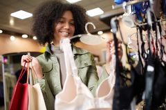 Young smiling attractive african american woman choosing right bra size in lingerie store. Black mixed race pretty girl Royalty Free Stock Photography