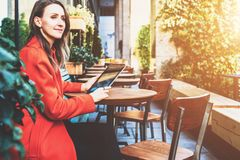 Young smiling attractive woman in orange coat is sitting outside in cafe at table and uses tablet computer. Royalty Free Stock Photography
