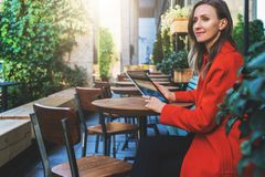 Young smiling attractive woman in orange coat is sitting outside in cafe at table and uses tablet computer. Royalty Free Stock Photos