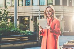 Young smiling attractive woman in orange coat is standing on city street and uses tablet computer. Girl checking email Royalty Free Stock Photography