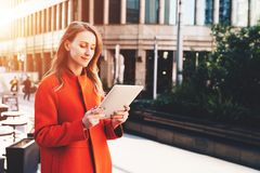 Young smiling attractive woman in orange coat is standing on city street and uses tablet computer. Girl checking email Stock Photo