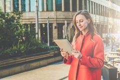 Young smiling attractive woman in orange coat is standing on city street and uses tablet computer. Girl checking email Royalty Free Stock Photos