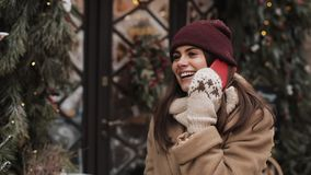 Young smiling attractive woman wearing winter hat and mittens, standing outside and talking on the phone laughing stock video footage