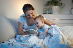 Young smiling with baby boy watching cartoons on digital tablet before going to sleep Royalty Free Stock Image