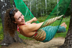 Young smiling barefooted woman swings in hammock. Head turned back stock images
