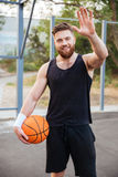 Young smiling bearded basketball player greeting somebody with hand waving Stock Images