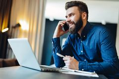 Young smiling bearded businessman sitting in front of computer, talking on cell phone, holding pen. Phone conversations. Young smiling bearded businessman is Royalty Free Stock Photo