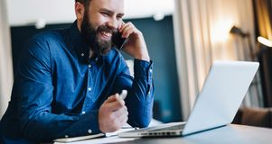Young smiling bearded businessman sitting in front of computer, talking on cell phone, holding pen. Phone conversations. Young smiling bearded businessman is Royalty Free Stock Photos