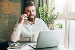 Young smiling bearded businessman is sitting at table in front of laptop, drinking coffee, talking on cell phone. Telephone conversations, distance work Royalty Free Stock Images