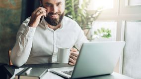 Young smiling bearded businessman is sitting at table in front of laptop, drinking coffee, talking on cell phone. Telephone conversations, remote work, online Stock Photo
