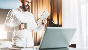 Young smiling bearded businessman standing near table in front of laptop, using digital tablet, drinking coffee. Man checks e-mail, blogging, chatting. Online Royalty Free Stock Photo